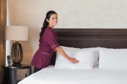 Happy hotel maid at work in hotel room